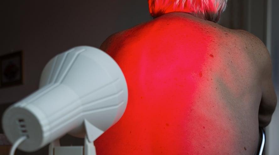 Eine Rotlichtlampe ist auf den Ruecken einer  oberkoerpfreien Person gerichtet