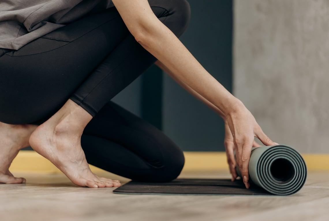 Frau rollt Yogamatte am Boden aus