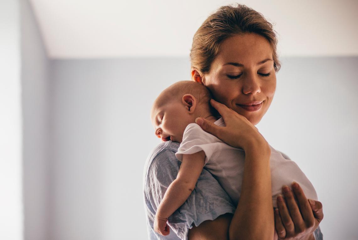 Eine Frau haelt ihr Baby ueber die Schulter und laechelt das Baby gaehnt