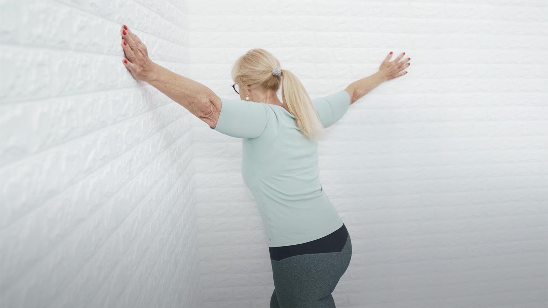 Herr Liebscher, der Schmerzspezialist, zeigt einer blonden Frau an einer Wand eine Uebung gegen Nackenschemrzen