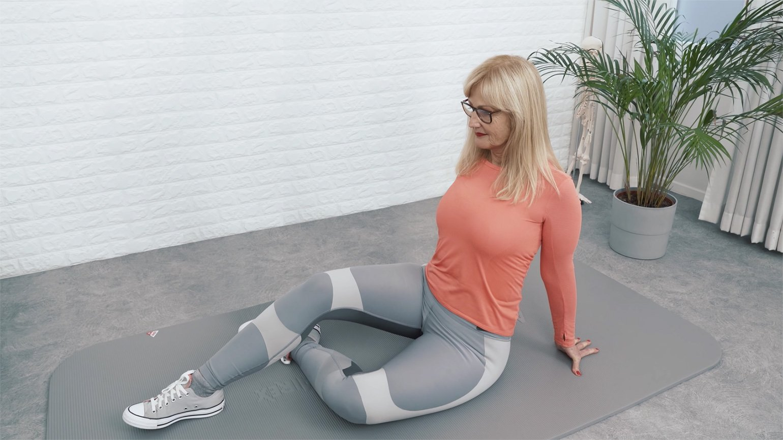 Eine Frau in Trainingsklamotten macht Uebungen gegen Rueckenschmerzen