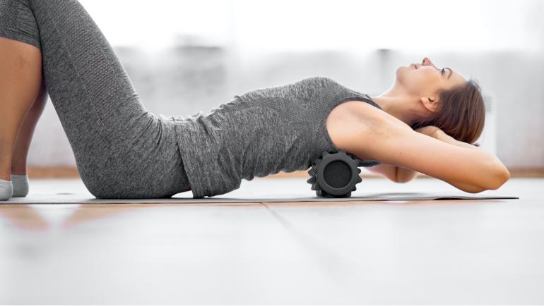 Eine Frau liegt am Boden auf einer Sportmatte in grauen Sportklamotten auf einer Faszienrolle die Hände hinter dem Kopf verschränkt