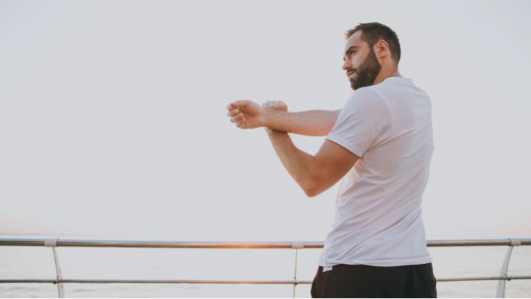 Ein Mann in weißen T-Shirt dehnt seinen rechte Schulter mithilfe seines linken Armes