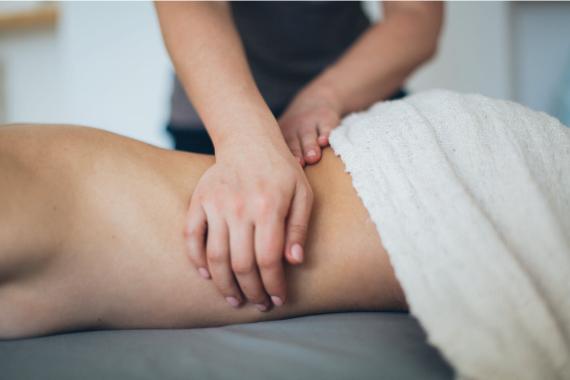 Eine Person liegt auf einer Massagebank und wird von einer anderen massiert