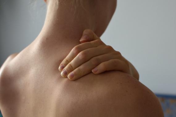 Nahaufnahme des Rueckens einer Frau, die sich mit der linken Hand den rechten Schulter Nacken Bereich haelt