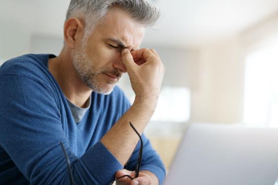 Mann im blauen Pullover und grauen Haaren hält sich mit dem rechten Daumen und Zeigefinger das Nasenbein