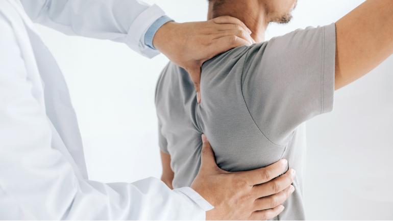 Ein Mann hebt im stehen seinen rechten Arm an er wird von hinten von einem Arzt abgetastet