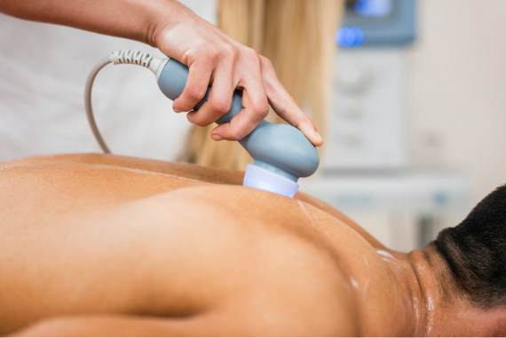 Ein Mann in weiß haelt einem Patienten auf der Liege ein Geraet zur Lockerung der Muskulatur in den Ruecken