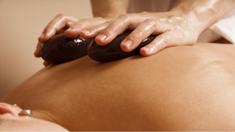 Nahaufnahme eines Rückens, der von einer Person mit oeligen Händen mit warmen Steinen massiert wird