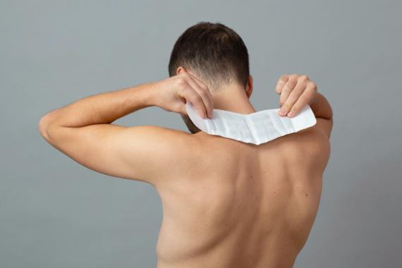 Mann mit freiem Oberkörper fixiert ThermaCare® Wärmepflaster am Nacken