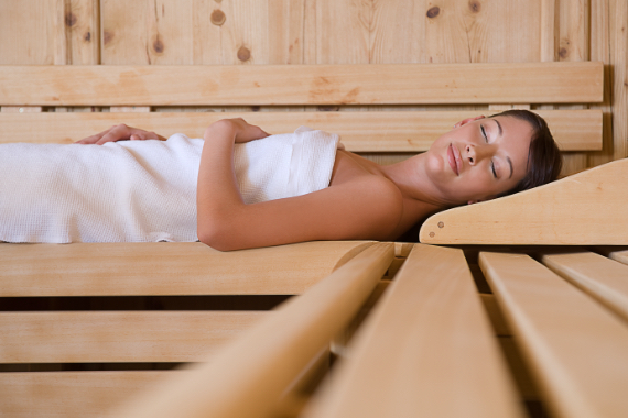 Eine Frau liegt in der Saune auf den Sitzbaenken in einem weißen Handtuch