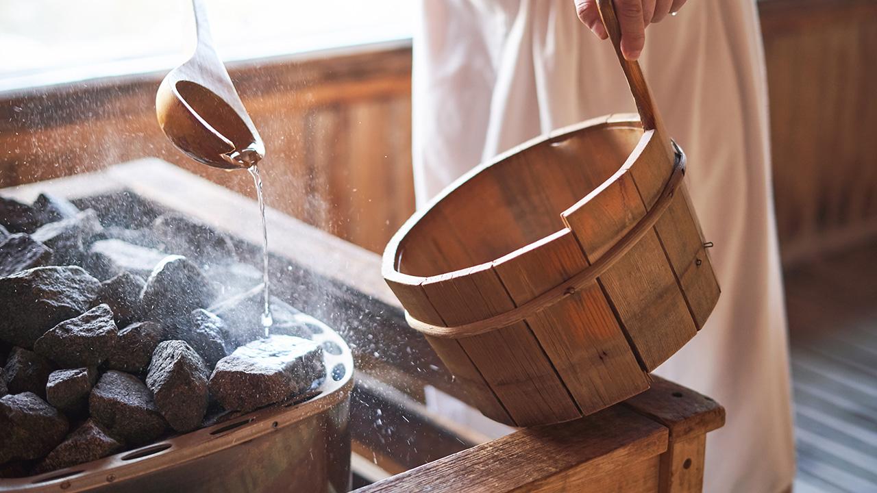 Person gießt in einer Sauna Wasser auf heiße Steine in